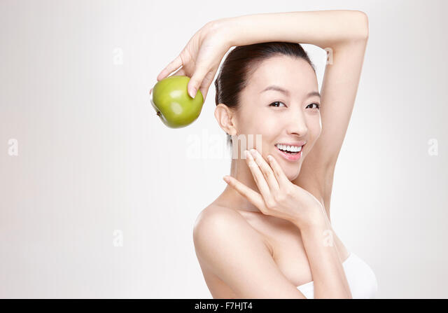 A smiling woman holding a green apple - Stock Image