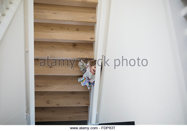 Overhead view of cute girl hiding on staircase - Stock Image