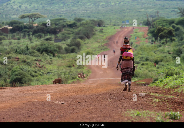 KAISUT, KENYA - May 19. A Samburu woman with a bay strapped on her back walks along a murram road at Kaisut, a remote - Stock Image