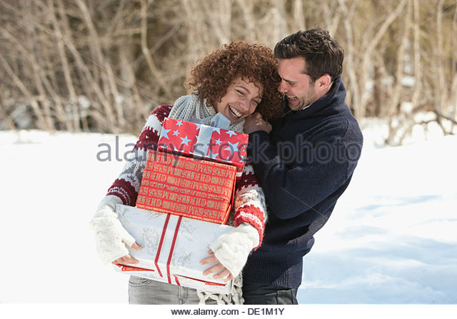 Man and woman with gifts outdoors, winter - Stock Image