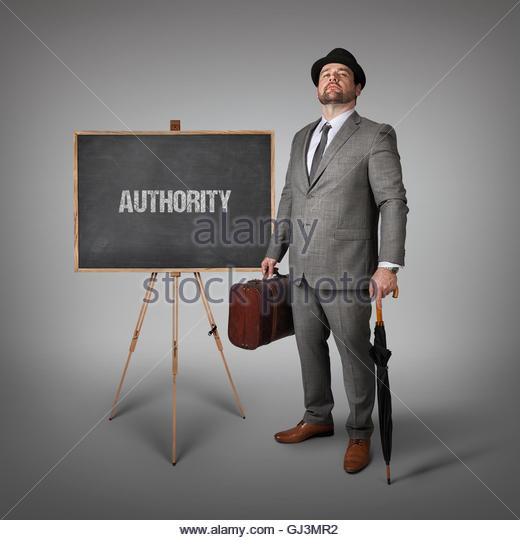 Authority text on blackboard with businessman - Stock Image