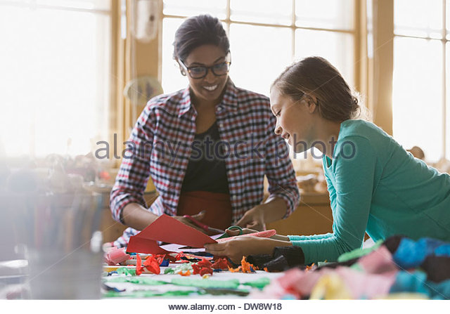 Teacher and girl cutting paper in art class - Stock Image