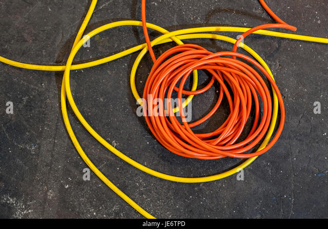 Electrical color cables lay in rolls over black ground - Stock Image