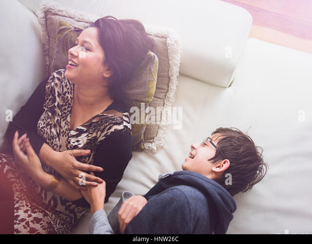 Mother and son laying on sofa and laughing - Stock-Bilder