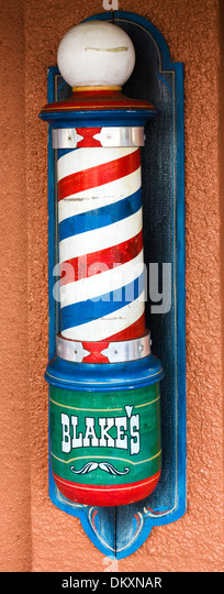 Old fashioned barber's pole outside a barber shop on First Street in historic downtown Fort Myers, Florida, - Stock Image
