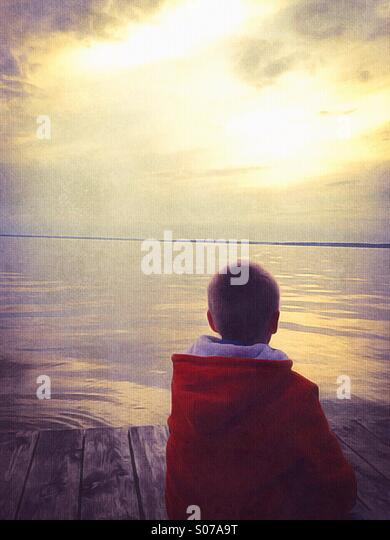 Boy on a dock watching the sunset - Stock Image