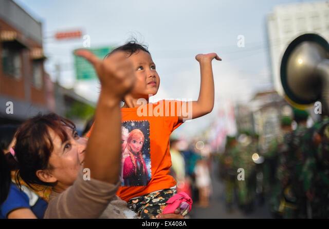Young girl cheering street parade. - Stock Image