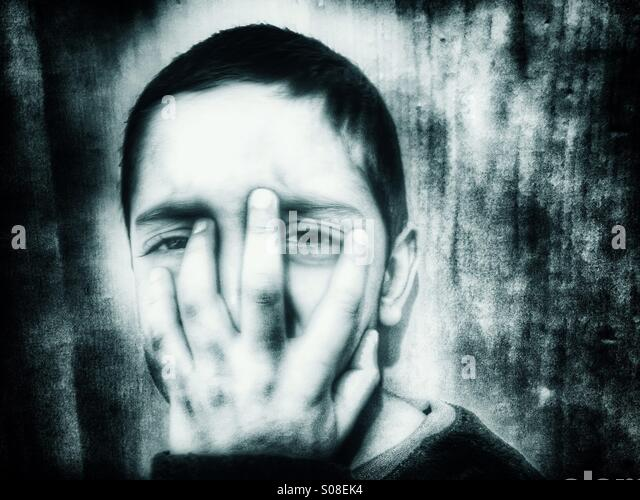 Scared boy hiding face - Stock Image
