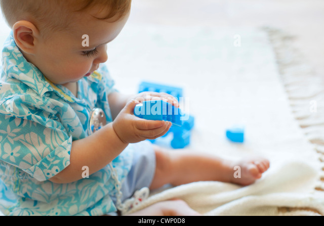 Baby boy playing with building blocks - Stock Image