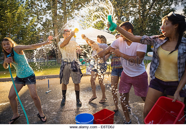 Playful friends splashing at charity car wash - Stock-Bilder