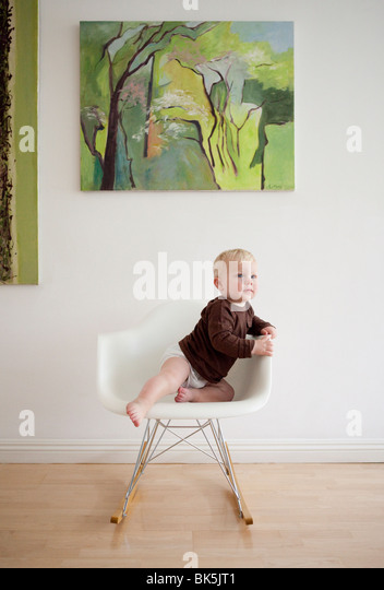 Baby in brown shirt on modern rocking chair - Stock Image