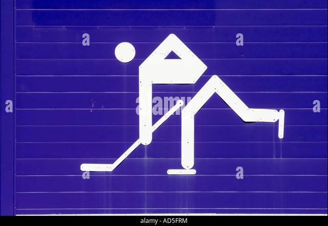 white ice hockey player symbol on blue wall - Stock Image