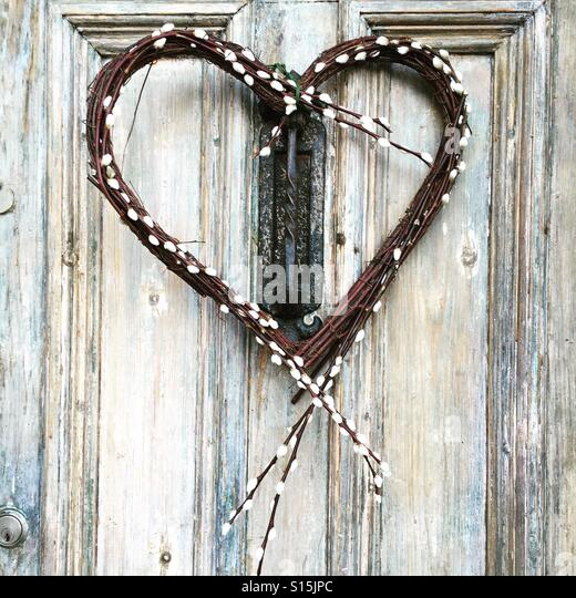 Homemade willow heart wreath on a door - Stock-Bilder