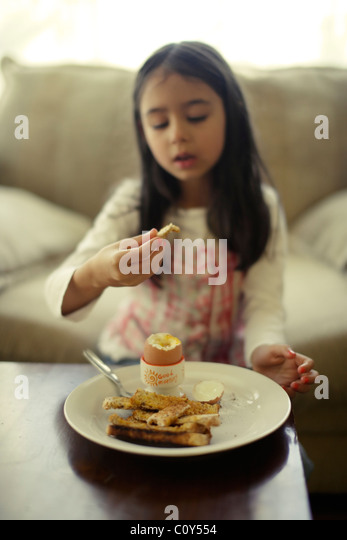 Girl eats boiled egg with toast soldiers for breakfast - Stock Image