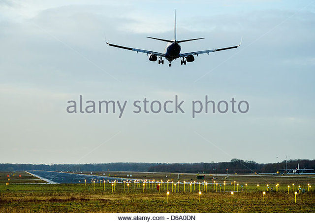 Plane flying over airport runway - Stock Image