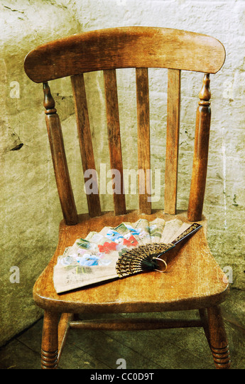 Old fashioned hand fan over an old wooden chair - Stock Image