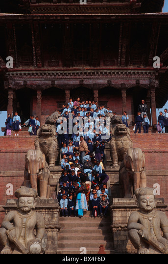 Nyatapola temple pagoda wrestler Jaya time and Patta stone stairs school class girl boy school uniform first-c - Stock Image