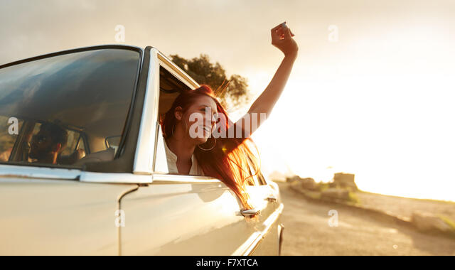 Shot of beautiful young woman enjoying road trip on a summer day. Excited young female raising her hand out of the - Stock-Bilder