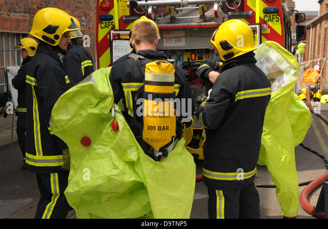 Firefighters check their breathing apparatus at the scene of an accident. - Stock Image