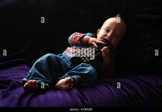 Six month old baby boy with the remote control on the couch - Stock Image