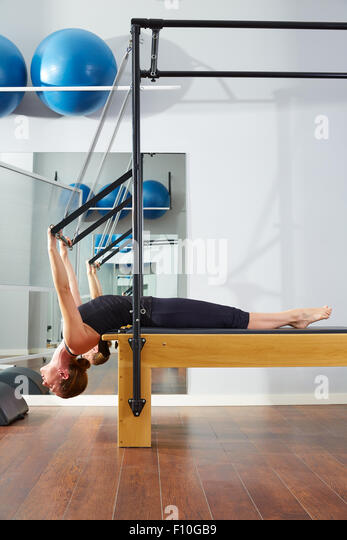 Pilates woman in reformer exercise at gym indoor - Stock-Bilder