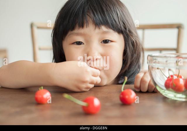Girl eating cherries, portrait - Stock Image