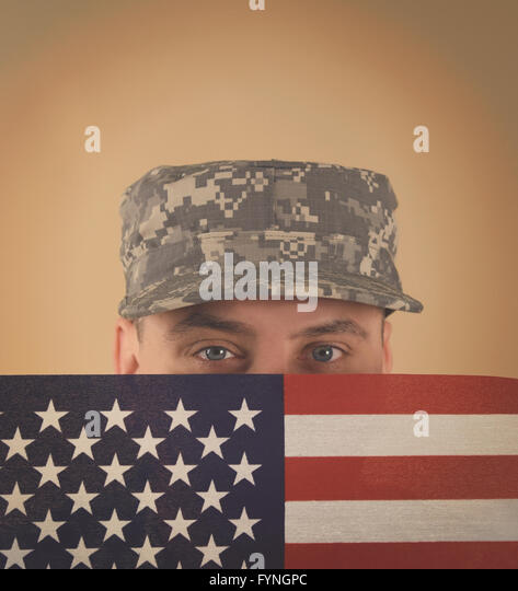 A military army soldier is holding an American flag up to his face for a veteran, memorial or freedom concept - Stock Image