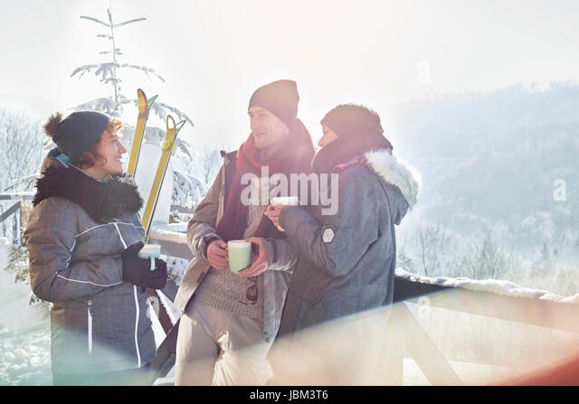 Skier friends talking, drinking coffee and hot cocoa apres-ski - Stock-Bilder