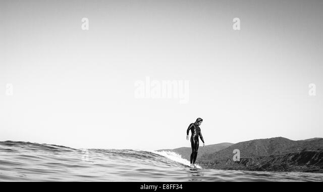 USA, California, Los Angeles County, Malibu, Surfer sliding on water - Stock Image