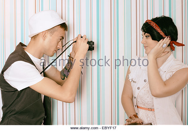 young guy photographer hipster and young beautiful model woman - Stock Image
