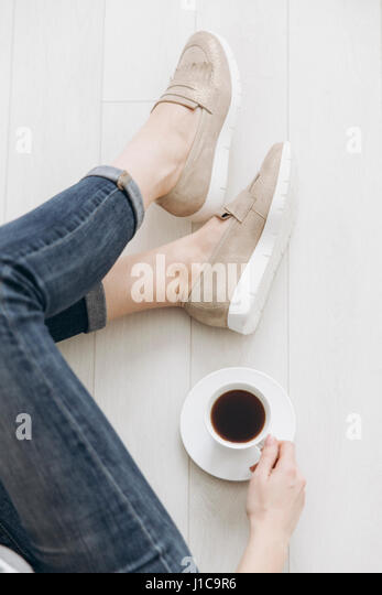 Legs of woman sitting on wooden floor drinking coffee - Stock Image