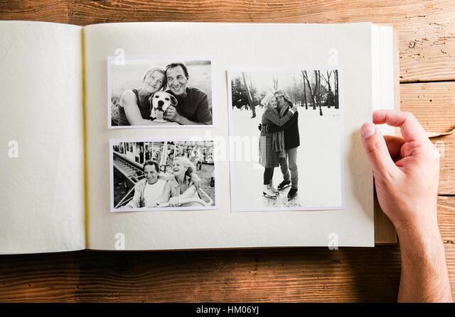 Hand holding photo album with pictures of senior couple. Studio - Stock Image