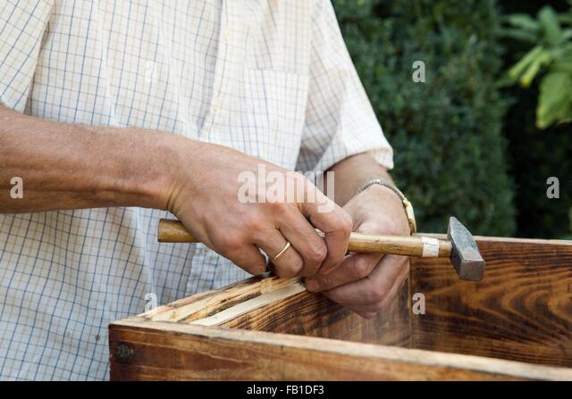 Senior man making wooden crate in garden, mid section - Stock Image