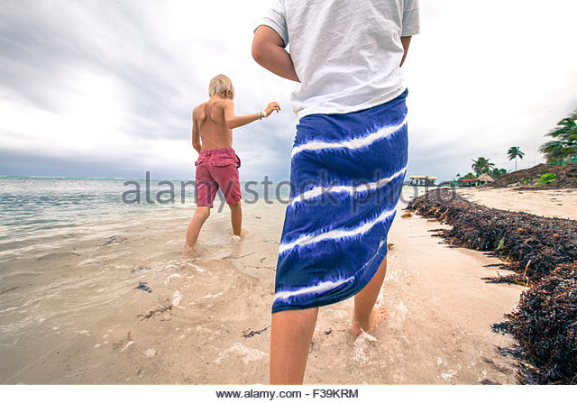 Two children walking in the shallow water at the beach, Belize - Stock Image