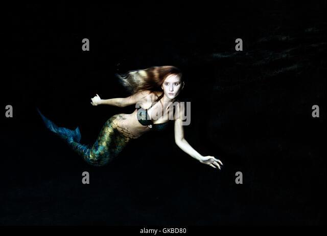 Mermaid swimming in dark water - Stock Image