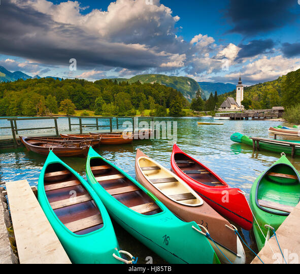 Bohinj Lake with boats and Church of St John the Baptist, Triglav National Park, Slovenia. - Stock Image