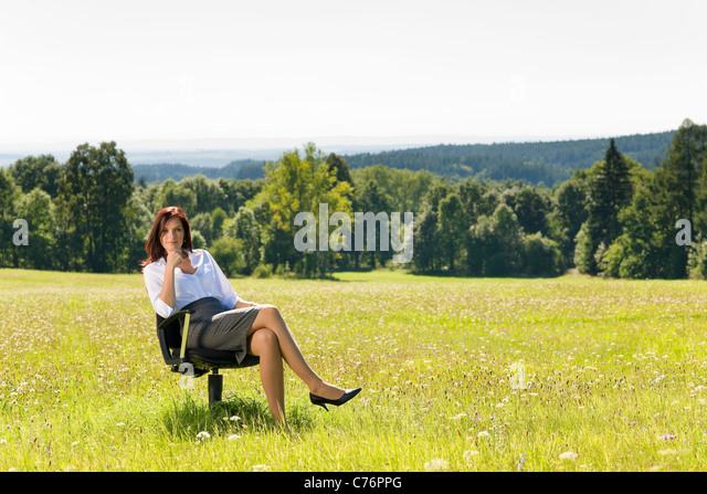Young businesswoman sitting armchair outside in middle of sunny meadow - Stock Image