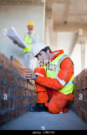 Worker laying brick at construction site - Stock Image