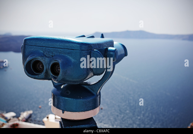 Coin operated binocular against harbor of Fira, Santorini island, Greece. - Stock Image