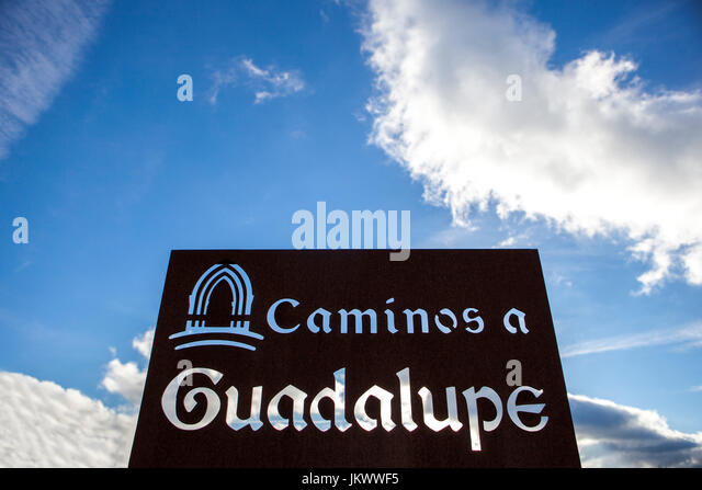 Metal sign post on Guadalupe Pilgrimage way, over blue cloudy sky - Stock Image
