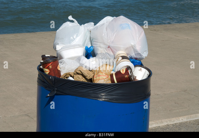 Trash overflows the top of a trash collection bin. - Stock Image