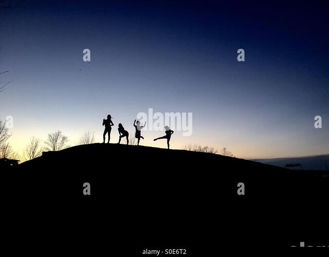 Children dancing in the sunset - Stock Image