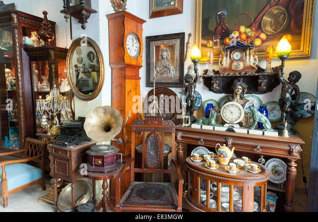 Old antique wood furniture and household items in antiques shop, Seville, Spain - Stock Image