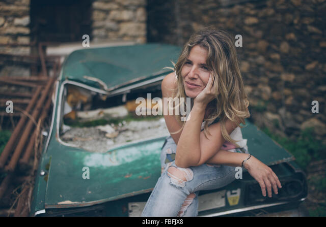 Young Woman Looking Away While Sitting On Abandoned Car - Stock-Bilder
