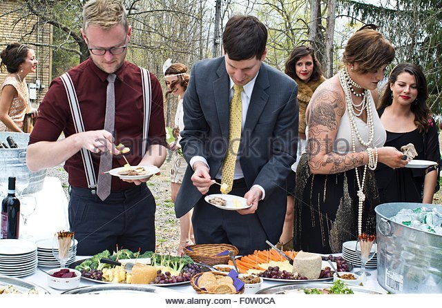 Wedding guests selecting food from buffet table - Stock Image