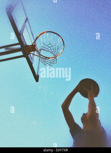 Teenage boy shooting a basketball. Outdoors shot, natural light, grainy edit. - Stock Image
