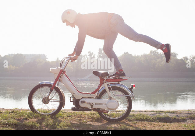 Mid adult riding moped, doing stunt, beside lake - Stock Image