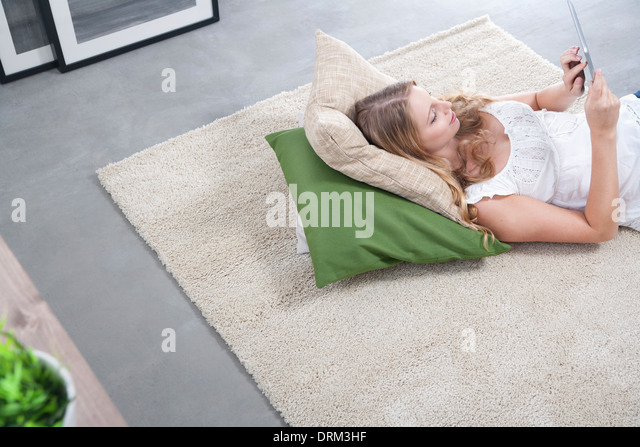 Young woman with tablet computer lying on carpet - Stock Image
