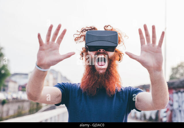 Portrait of young male hipster with red hair and beard screaming whilst wearing virtual reality headset - Stock Image