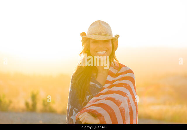 Portrait of mature woman outdoors, wearing cowboy hat, wrapped in American flag, smiling - Stock-Bilder